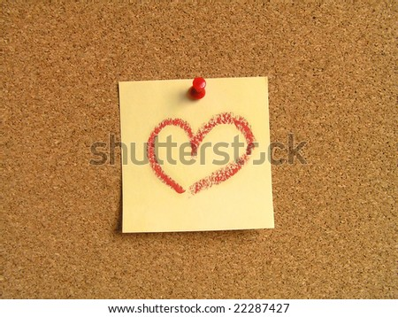 Yellow small sticky note on an office cork bulletin board. The heart painted with a lipstick - stock photo