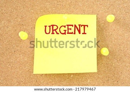 Yellow small sticky note on an office cork bulletin board. Urgent - stock photo