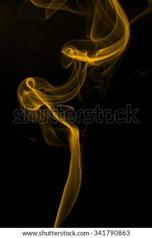 Yellow smoke abstract dark background - stock photo