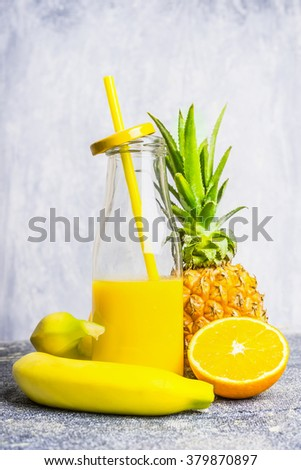Yellow smoothie bottle with straw and ingredients on light wooden background, side view. Healthy lifestyle and detox or diet  food concept - stock photo