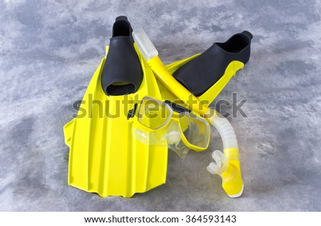 yellow snorkel mask and fins snorkeling gear isolated against gray background - stock photo