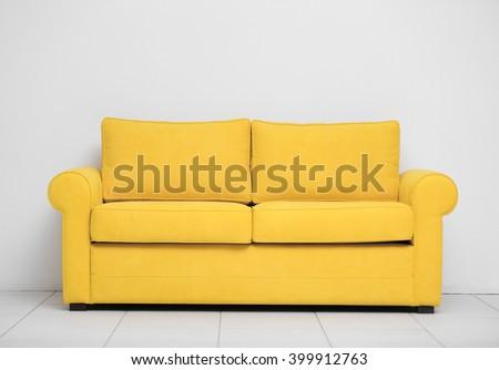 Yellow sofa on white wall background - stock photo