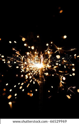 yellow sparkler with fire particles - stock photo