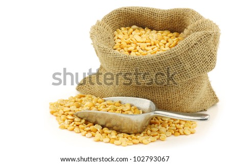 yellow split peas in a burlap bag with an aluminum scoop on a white background - stock photo