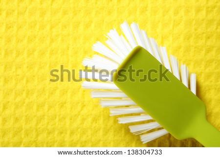 Yellow sponge background and cleaning brush - stock photo