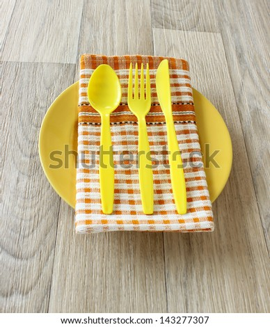 yellow spoon, fork, knife and napkin on yellow plate - stock photo
