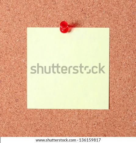 yellow sticker pinned on a cork bulletin board - stock photo