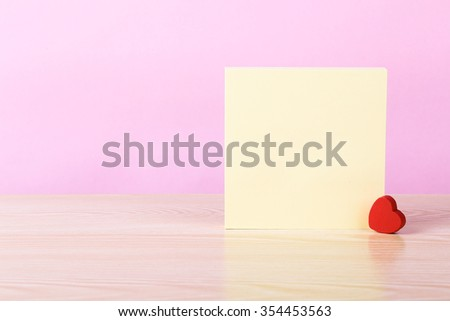 Yellow sticky note book with love heart against pink background. - stock photo