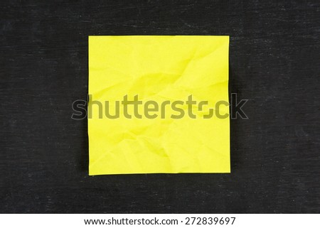 Yellow sticky note on chalkboard - stock photo
