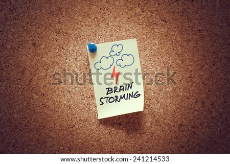yellow sticky reminder note with brain storming message on corkboard. - stock photo