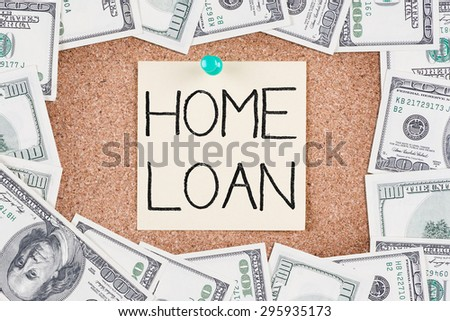 Yellow sticky reminder with HOME LOAN message on corkboard with border made of 100 US dollars - stock photo
