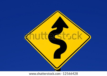 Yellow street sign with curves against blue sky - stock photo