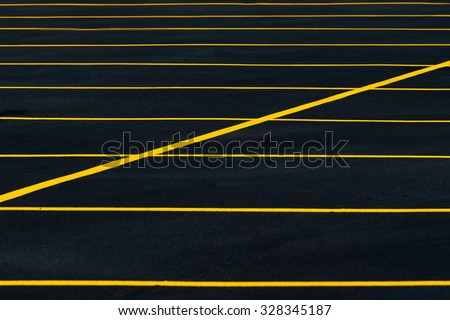 Yellow stripes on black parking lot - stock photo