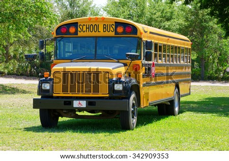 Yellow summer camp school bus is parked in a grass field with a dirt road and woods in the background - stock photo