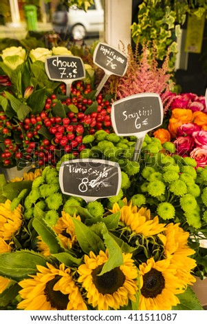 Yellow sunflowers for sale in Paris flower shop, with labels in euros - stock photo