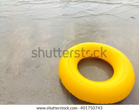 Yellow swim ring floating on a sea - stock photo