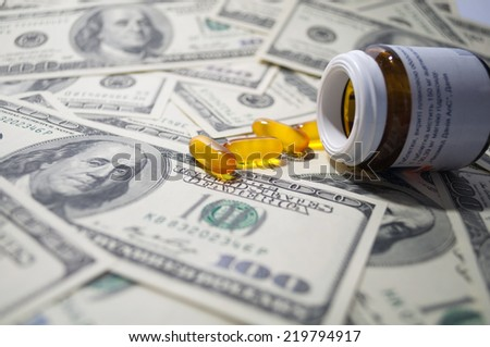 yellow tablet scattered on the bills of $ 100 - stock photo
