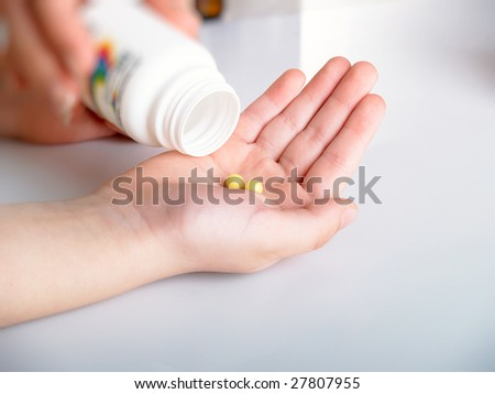 Yellow tablets in a children's hand - stock photo