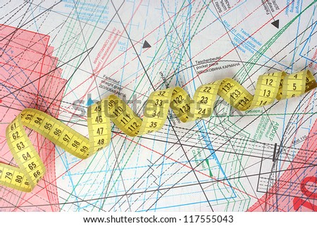 yellow tailor measuring tape on patterns of clothing - stock photo