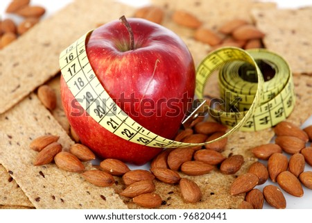 Yellow tailoring meter wrapped around an apple with some diet biscuits and almonds - stock photo