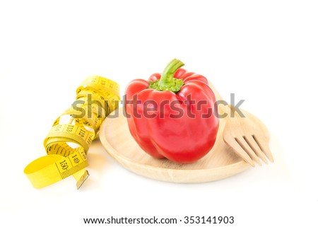 Yellow tape measure and sweet red pepper in wooden plate on white background. Healthy lifestyle concept - stock photo