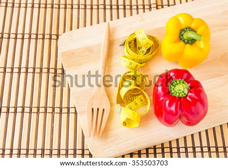 Yellow tape measure and sweet red pepper on wooden plate. Healthy lifestyle concept - stock photo