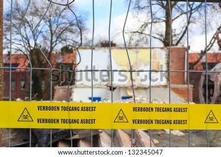 Yellow tape with Dutch text 'no trespassing asbestos' on demolition site - stock photo