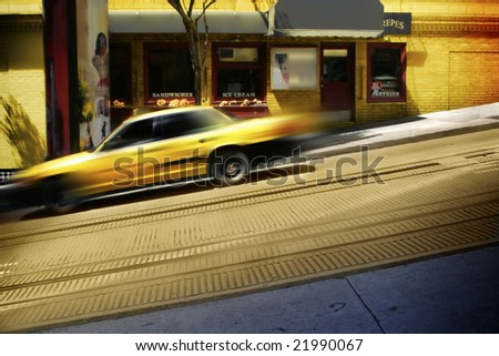 Yellow taxi cab speeding down steep inclined city street - stock photo