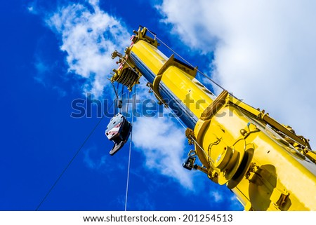 Yellow telescopic arm of a mobile crane against deep blue sky and white clouds - stock photo
