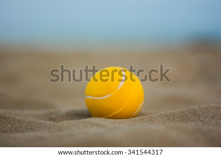 yellow tennis ball on the beach in the sand - stock photo