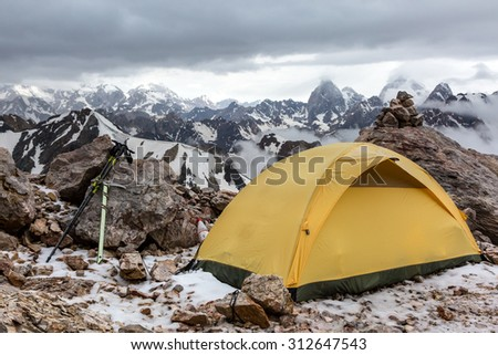 Yellow tent on mountain landscape. Small Alpine camping Tent located on rocky terrain stone surface and high mountain hills and peaks on background evening sun light - stock photo