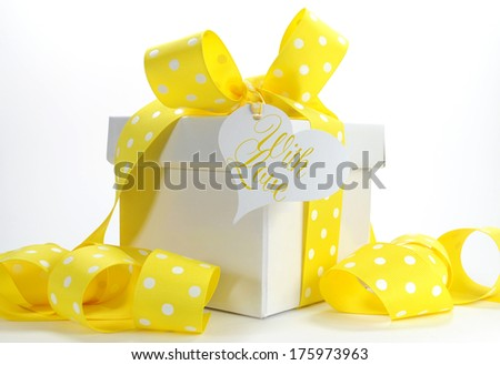 Yellow theme gift box with yellow polka dot ribbon and white copy space for Easter, birthday, wedding, baby or bridal shower present. - stock photo