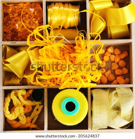 Yellow thread and material for handicrafts in box isolated on white - stock photo