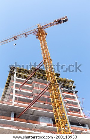 Yellow tower crane and unfinished building against blue sky - stock photo