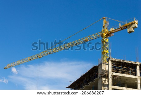 Yellow tower crane on blue sky background. Crane is building skyscraper in site. - stock photo