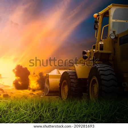 Yellow tractor in a field during sunrise - stock photo