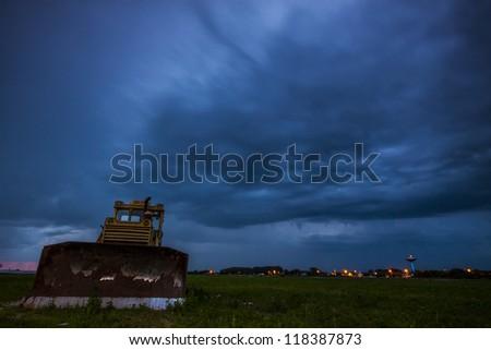 Yellow tractor on dramtic sky background - stock photo