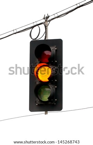 Yellow traffic light hanging from wires overhead. Close up on a white background. - stock photo