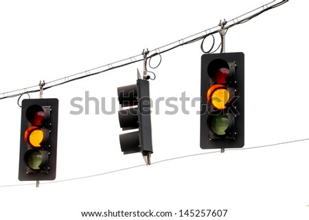 Yellow traffic lights hanging from wires overhead. Close up on a white background. - stock photo