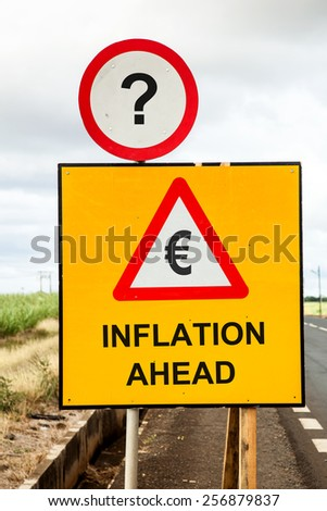 Yellow traffic sign and a red warning triange with the message Euro Inflation ahead beside the road. Business or financial concept asking if inflation threatens. - stock photo