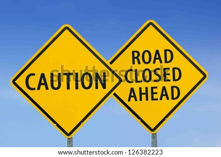 """Yellow traffic sign """"caution"""" and """"Road closed ahead"""" on the sky background - stock photo"""