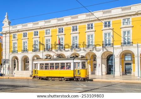 Yellow tram on a square Praca de Comercio in Lisbon, Portugal - stock photo