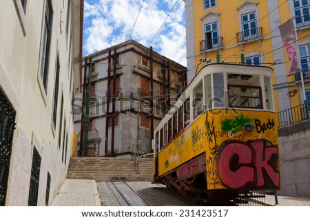 yellow tram on narrow street of Alfama, Lisbon, Portugal  - stock photo