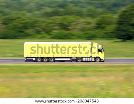 yellow truck driving on a road - slow shutter  - stock photo
