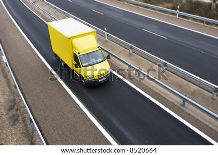 Yellow truck on highway - stock photo