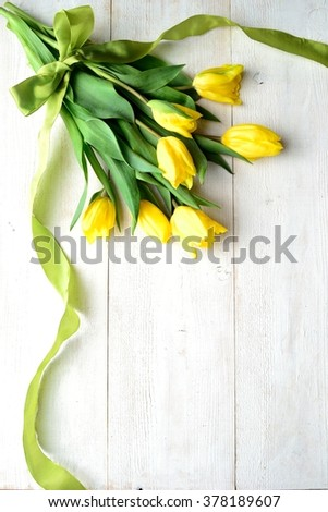 Yellow tulip bouquet with yellow green ribbon on the white wooden background - stock photo