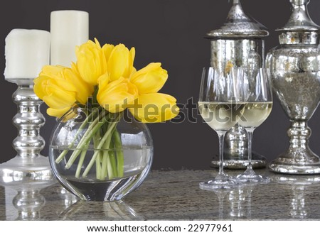 yellow tulips in vase with glasses of wine & home decor accessories - elegant tablescape - stock photo