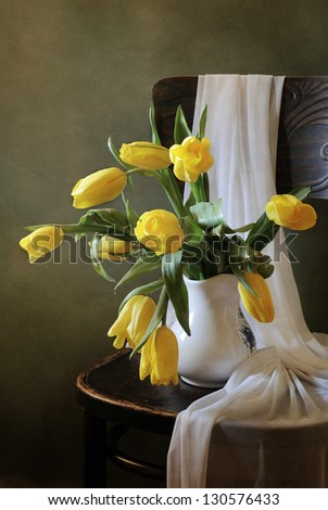 Yellow tulips on a chair - stock photo