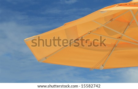 Yellow umbrella and blue sky - stock photo