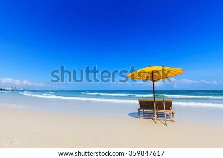 Yellow umbrella and wooden chairs on Hua Hin beach, Thailand - stock photo